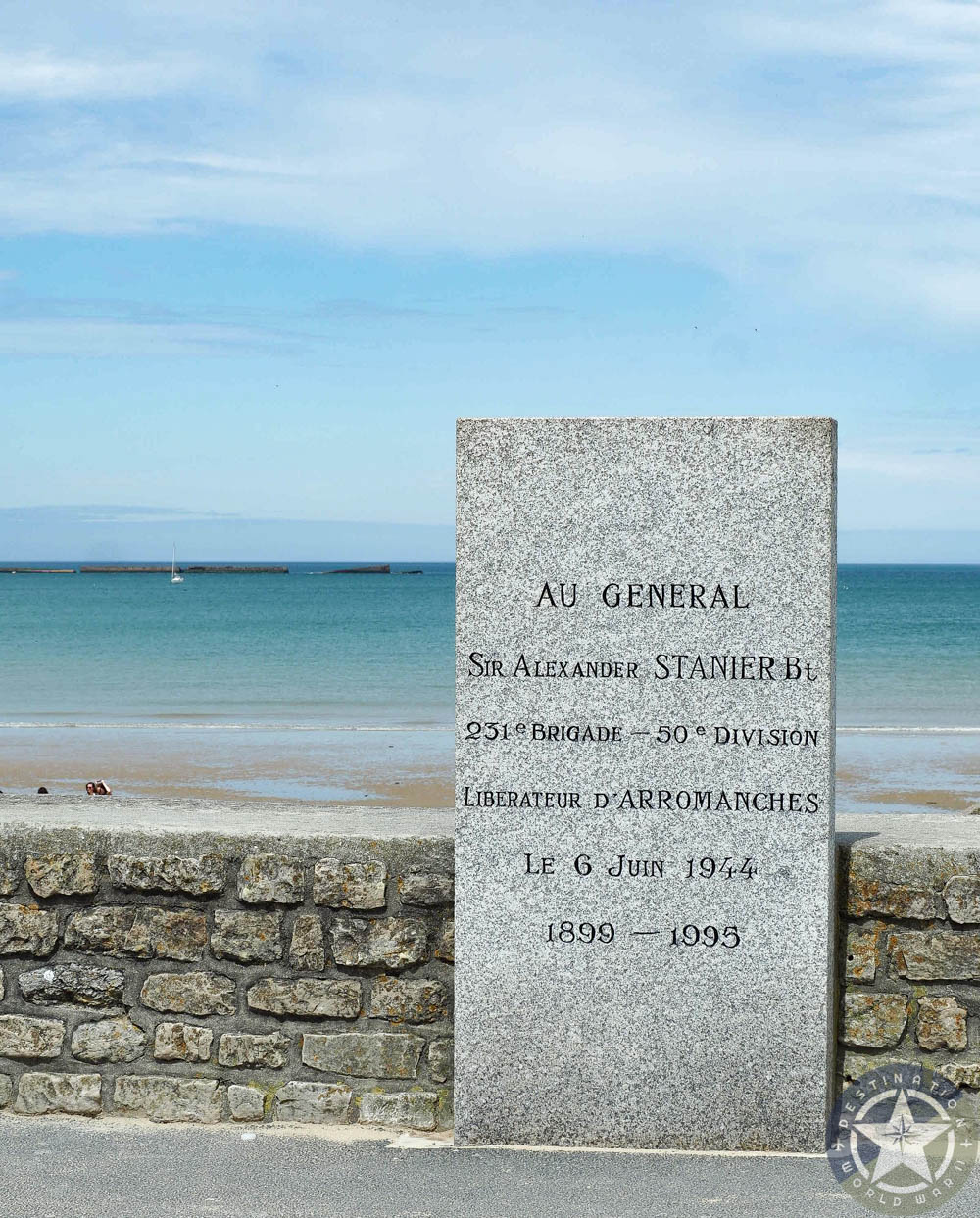 stone memorial in front of stone wall in front of gold beach normandy