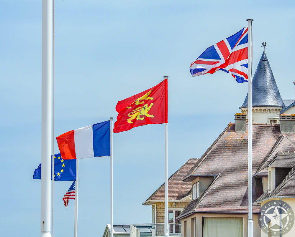 French, British, Normandy, and EU flags at Arromanches-les-Bains