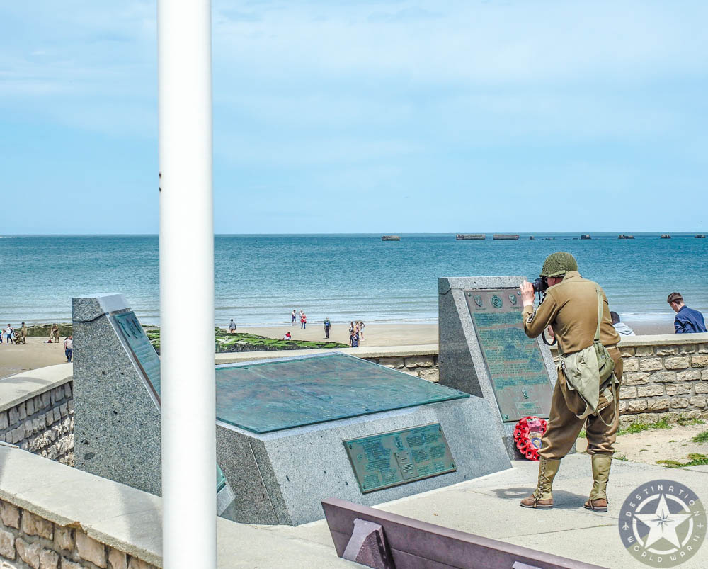 Man in WWII soldiers uniform photographing a memorial in front of gold beach normandy